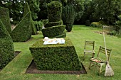 AFTER THE PARTYS OVER. LEANING CUBE WITH TEA PARTY,  PLUS THE TOPIARISTS TOOLS,   TAXUS BACCATA. TOPIARY GARDEN