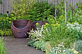 WOODEN CUP SEATS ON PAVED AREA. BAMBOO,  GRASSES,  EUPHORBIA,  GERANIUMS. WALKING BAREFOOT WITH BRADSTONE,  DES. SARAH EBERLE