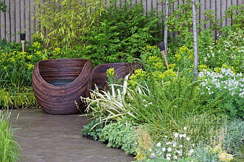 WOODEN_CUP_SEATS_ON_PAVED_AREA_BAMBOO__GRASSES__EUPHORBIA__GERANIUMS_WALKING_BAREFOOT_WITH_BRADSTONE