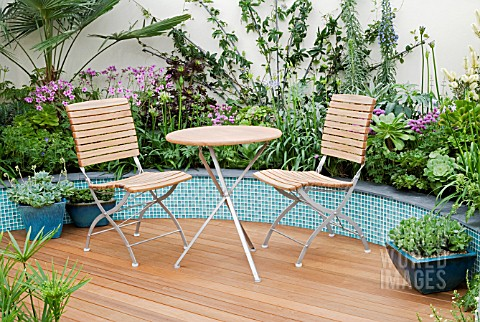 TABLE__CHAIRS_ON_DECKING_WITH_CERAMIC_TILE_RAISED_BORDERS_BEHIND_MITIE_GARDEN__DES_JO_PENN_INC_