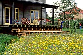 VERANDAH AND STEPS LEADING DOWN TO A COLOURFUL WILDFLOWER MEADOW. FATHER & CHILD PLAYING BADMINTON ON LAWN.