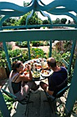 COUPLE EATING IN THEIR GAZEBO. IN POTAGER GARDEN