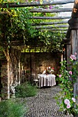 TABLE SET FOR A MEAL OVERHUNG BY A WOODEN PERGOLA. BORGO SANTO PIETRO, TUSCANY