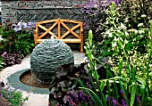 SMALL GARDEN WITH SLATE WATER SPHERE, WOODEN BENCH,  GALTONIA CANDICANS