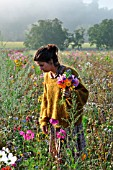 Young woman making a bouquet in a flower meadow