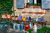Collection of watering cans on a bench, Provence, France