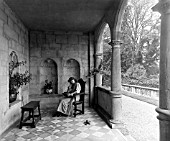 A YOUNG WOMAN READING IN THE LOGGIA AT CRANBORNE MANOR - 1901