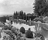 AN ELEGANT WOMAN WALKS PAST THE WATER GARDEN KNOWN AS THE WHITE SEA AT SEDGWICK PARK. 1901
