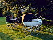 A COUPLE OF OLD FASHIONED PRAMS IN THE GARDEN AT NESS HALL