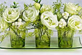 GREEN AND WHITE FLOWER ARRANGEMENT IN GREEN GLASSES