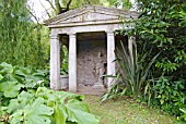 TEMPLE AT MANNINGTON HALL GARDEN, NORFOLK WITH PETASITES, LAURELS AND PHORMIUM