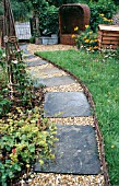 GRAVEL PATH WITH PAVING INSETS,  WITH OBELISK,  WICKER SEAT AND BEE HIVE,  WATTLE EDGING.