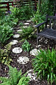 ROUND STEPPING STONES THROUGH FERNERY; AND WOODEN BENCH; RIPPINGALE; LINCS.