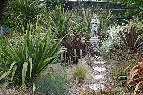 ROUND_STEPPING_STONES_THROUGH_MIXED_GRASSES_PHORMIUM_AND_YUCCA_PLANTING_AND_STONE_STATUE_FEATURE_RIP
