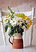 WHITE AND YELLOW FLOWER ARRANGEMENT IN JUG ON RUSTIC WHITE TABLE