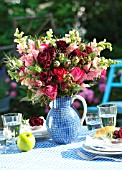 BOUQUET OF ROSES IN A BLUE JUG ON A SET TABLE WITH AN APPLE
