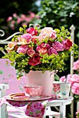 A BOUQUET OF ROSES IN A PINK BUCKET ON THE BALCONY TABLE