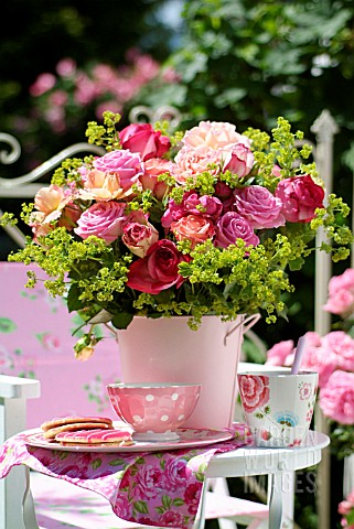 A_BOUQUET_OF_ROSES_IN_A_PINK_BUCKET_ON_THE_BALCONY_TABLE