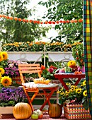 COLOURFUL AUTUMNAL BALCONY WITH CONTAINER PLANTS AND FURNITURE