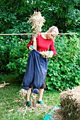 BUILDING A SCARECROW:FILL TROUSERS WITH STRAW