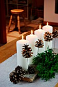CHRISTMAS DECORATION WITH CANDLES, FIR BRANCHES AND FIR CONES
