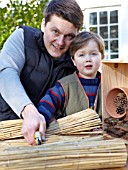 INSECT HOUSE BUILDING PROJECT WITH FATHER AND SON.  CUTTING BAMBOO INTO SMALL BUNDLES.  STEP 30