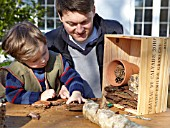 INSECT HOUSE BUILDING PROJECT WITH FATHER AND SON.  FILLING GAPS IN THE BOX WITH BARK.  STEP 17