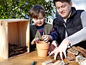 INSECT HOUSE BUILDING PROJECT WITH FATHER AND SON.  PLACING CONES IN POT.  STEP 10
