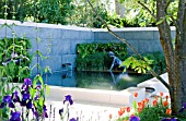 TRANQUIL POOL AND BRONZE STATUE OF VOLTAIRES CUNEGONDE FROM CANDIDE  TULIPA ORANGE EMPEROR AND BLUE IRIS WITH QUERCUS CERRIS LEAVES.  FOREIGN AND COLONIAL INVESTMENTS GARDEN.  DESIGNER THOMAS HOBLYN, RHS CHELSEA