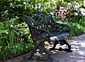 ORNATE IRON BENCH ON BRICK PATH IN SPRING GARDEN