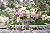 MALUS X EVERESTE WITH OUTDOOR TABLE SET UNDER APPLE BLOSSOMS AND DECORATED WITH FLORAL ARRANGEMENTS OF RANUNCULUS AND ROSES