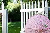 CHINESE SILK PARASOL IN GARDEN WITH WHITE PICKET FENCE AND GATE