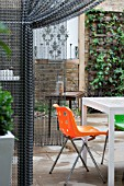 THE DRAWING ROOM GARDEN  URBAN LONDON GARDEN  CHAIN SCREEN DIVIDE WITH FURINTURE  DESIGNED BY: EARTH DESIGNS.