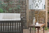 THE DRAWING ROOM GARDEN  URBAN LONDON GARDEN  SEATING AREA AROUND WATER FEATURE THRIUGH CHAIN SCREEN  DESIGNED BY: EARTH DESIGNS.