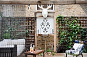 THE DRAWING ROOM GARDEN  URBAN LONDON GARDEN  THE SEATING AREA  WITH THE ILLUMINATED MOOSE HEAD TROPHY AND THE WATER FEATURE  DESIGNED BY: EARTH DESIGNS.