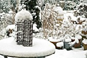SNOW COVERED GARDEN TABLE WITH RUSTY IRON ORNAMENT