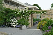 MODERN WALLED GARDEN WITH WHITE ROSES AND HERBACEOUS BORDERS LOOKING THROUGH TO KITCHEN GARDEN
