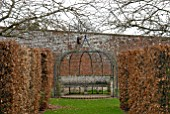 METAL ARBOUR AND STONE SEAT AT OZLEWORTH PARK, GLOUCESTERSHIRE