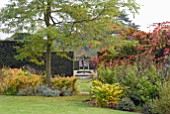 AUTUMNAL VIEW THROUGH YEW HEDGE OF STATUE AND LILY PONDS AT OZLEWORTH PARK, GLOUCESTERSHIRE