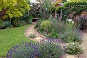 CURVED BRICK AND GRAVEL PATH IN SUBURBAN BACK GARDEN WITH COLOURFUL BORDERS AND LAWN