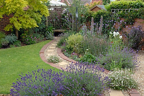 CURVED_BRICK_AND_GRAVEL_PATH_IN_SUBURBAN_BACK_GARDEN_WITH_COLOURFUL_BORDERS_AND_LAWN