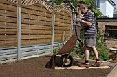 MAN ADDING TOPSOIL FROM WHEELBARROW