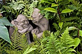 IMP STATUES SITTING IN AMONGST FERNS