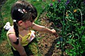YOUNG GIRL GARDENING WITH TROWEL