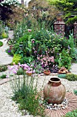 VIEW OF GARDEN WITH VASE AND ALLIUM SCHOENOPRASUM PLANTED,  IN GRAVEL AND CIRCULAR DESIGN. OWNERS,  MR & MRS CLARK