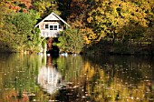 VIEW OF THE BOATHOUSE, AUTUMN COLOURS AND REFLECTIONS ON THE LAKE AT WINKWORTH ARBORETUM, SUSSEX