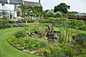 THE MAIN POND AND WATER FEATURE AT THE HOUSE OF PITMUIES GARDEN, SCOTLAND.