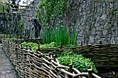 RAISED BED MADE WITH SMALL WILLOW HURDLES,  DESIGNED TO BE PLANTED AS POTAGER.