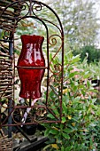ORNATE GARDEN LIGHT,  WROUGHT IRON SCROLLS WITH RED GLASS SHADE.