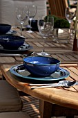 TABLE SET OUTDOORS WITH CUTLERY AND GLASSES.